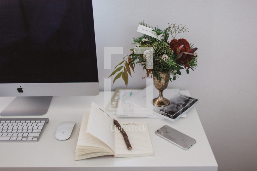 desk with notebook, computer, pencil, cellphone, books, and vase of flowers