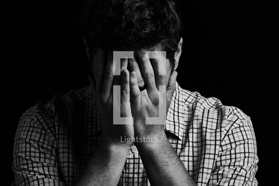 a sad man covering his face with hands