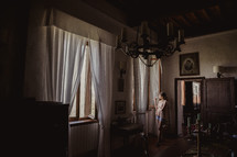 A woman looking out a window in a villa in Italy