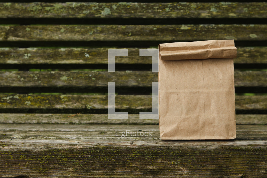 brown lunch bag on a wood bench
