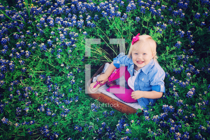 Happy little girl in field of purple wildflowers