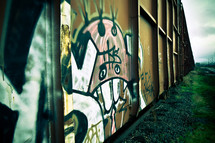 graffiti along the side of railroad box cars