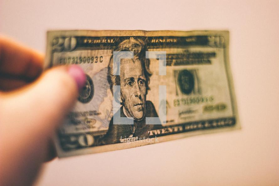 Hand holding a twenty dollar bill.