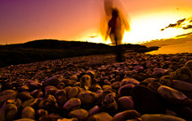 blurry shape of a person walking on a stone shore