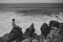 Woman sitting on rocky cliff overlooking the ocean waves.