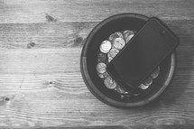 a bowl of coins and a phone