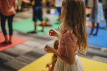 children standing on colored mats