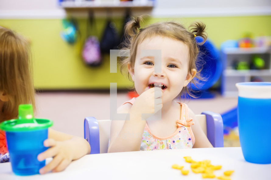 toddler eating a snack at preschool