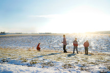 kids playing in a field after fresh snowfall