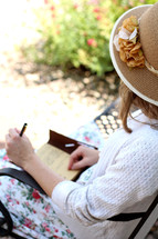 woman in a dress sitting on a park bench writing in a journal