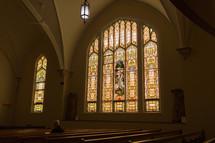an elderly man sitting alone in a church