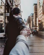couple walking on a sidewalk holding hands