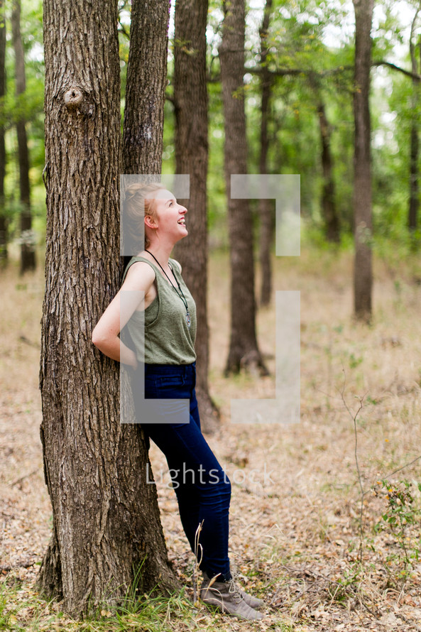 woman leaning against a tree in a forest