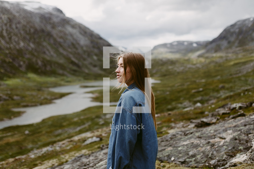 a woman standing on a mountainside in Norway