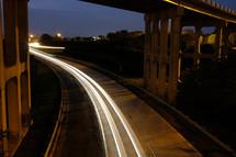 Lights along a highway under an overpass.