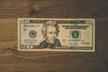 Twenty dollar bill on wood.