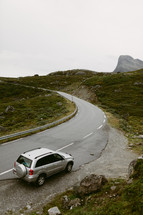 a car parked along the side of a curvy mountain road in Norway