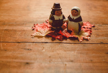 Pilgrim figurines on fall leaves on a wooden table -- Thanksgiving decor.