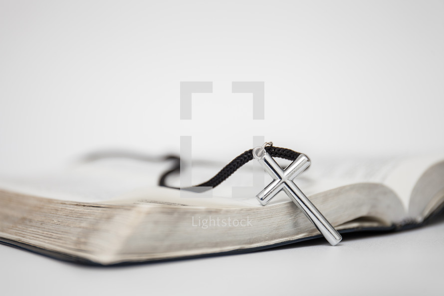 cross necklace on the pages of a Bible