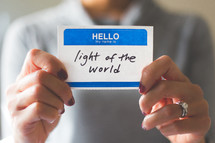 woman holding a name tag with the word light of the world