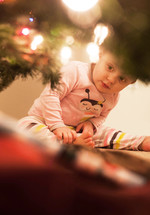 A toddler girl looking under a Christmas tree.
