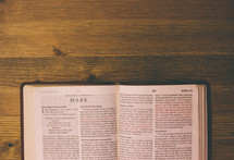 Bible open to Mark on a wooden table.