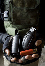 Man in military garb holding flashbang, fragmentation grenade, and shotgun cartridge.