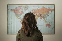 a woman standing in front of a world map