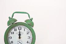 green alarm clock at noon