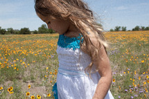 a young girl walking in a field of wildflowers