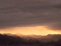 Light breaking through the darkness over rugged mountains