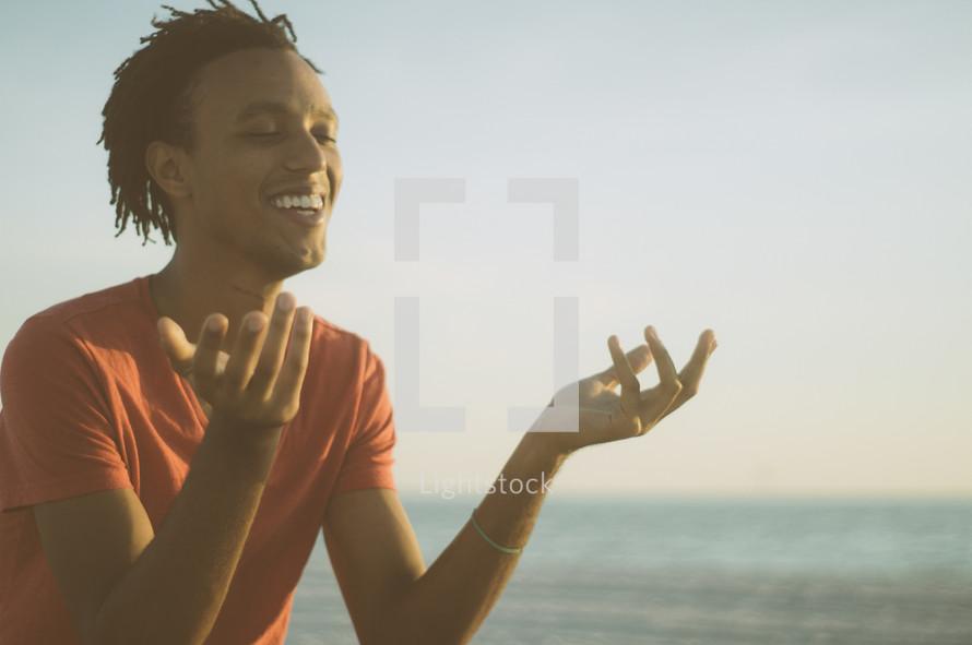 African-American man sitting on a beach meditating