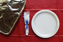 paper plate place setting and foil covered casserole