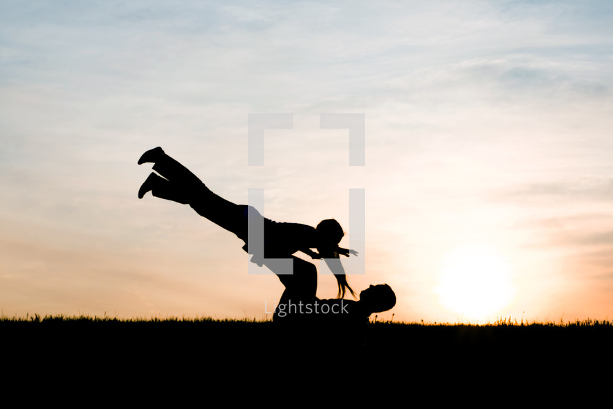 a father and daughter playing airplane