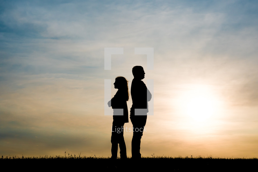 silhouettes of a couple standing back to back at sunset