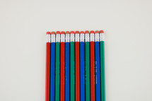 row of pencil erasers on a white background