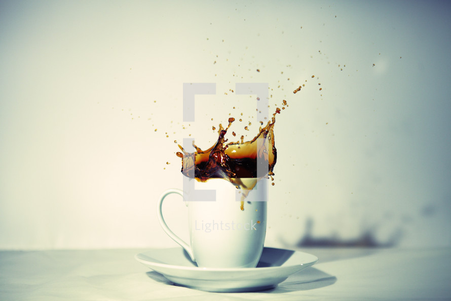 Hot coffee splashes from a white mug.