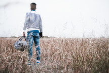 African-American man holding a backpack standing in a field