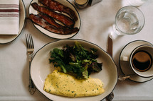 omelet, salad, greens, and bacon on a table