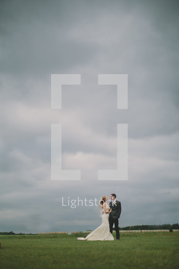 Bride and groom - field - cloudy sky