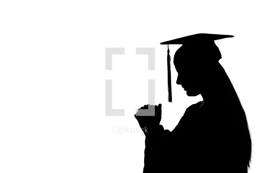 silhouette of a graduate in prayer