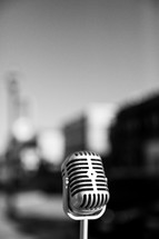 Retro microphone with a city in the background.