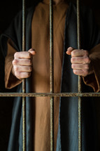 A man in Biblical garb holds onto prison cell bars.