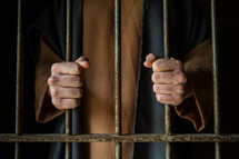 A man in Biblical clothing holds onto prison cell bars.
