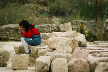 a little girl sitting on rocks crying