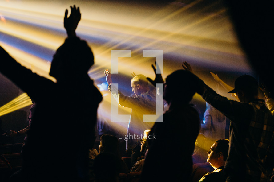 raised hands in an audience under the glow of spotlights