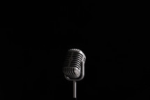 Vintage style microphone on black background.