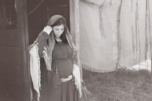Pregnant Mary standing by a stable