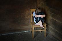 scared child hiding in a corner