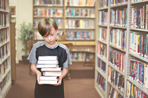 Boy carrying a stack of books in a library.